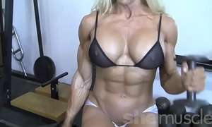 Sexy golden-haired female bodybuilder in watch throughout top works out